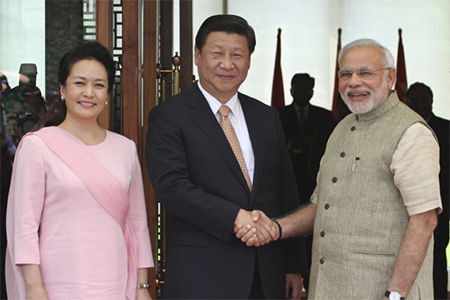 Indian PM Narendra Modi greets Chinese President Xi Jinping and his wife wife Peng Liyuan upon arrival at a hotel in Ahmadabad